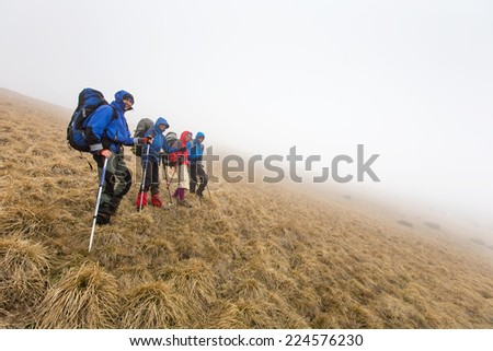 Group of hiker are walking in mountains covered with dense clouds