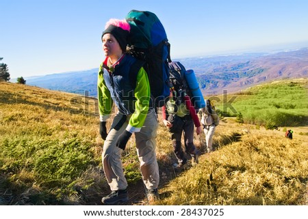 Group of hikers climbing up the rocky mountain - stock photo