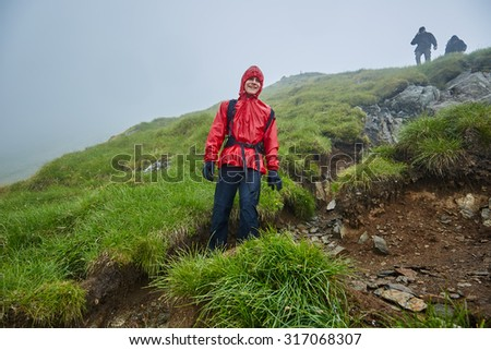 Group of hikers descending on a mountain with raincoats during rain