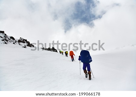 Group of hikers in the mountain. Climb to the top. winter hiking - stock photo