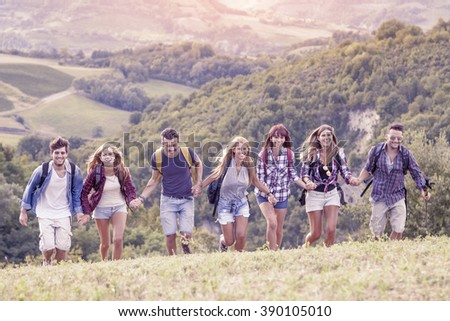 group of hikers in the mountain running holding hands - stock photo