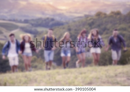group of hikers in the mountain running holding hands. blurred image - stock photo