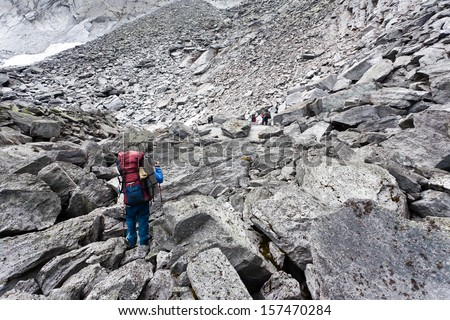 Group of hikers moving on wild meadows of Ural mountains, Russia.
