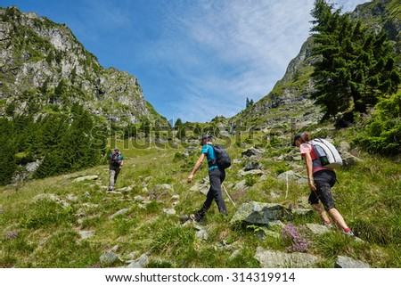 Group of hikers on a trail in the mountains in a beautiful scenery - stock photo