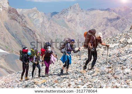 Group of Hikers Walking on Deserted Rocky Terrain Five Members Team Sport Clothing Going Heavy Load Backpacks Climbing Gear Up  Mountain Peaks Blue Sky Majestic Summits Shining Sun Background - stock photo