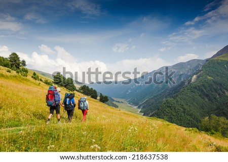 Group of hikers with backpacks walking in mountains. The sky is blue and cloudy. - stock photo