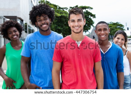 Group of hip and cool young adults laughing at camera in city - stock photo