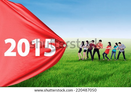 Group of hispanic business team drag number 2015, symbolizing a change for progress - stock photo