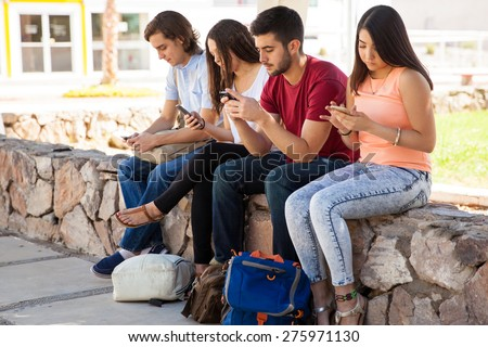 Group of Hispanic college students ignoring each other and using their cell phones - stock photo