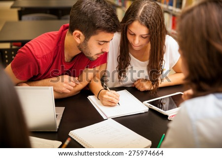 Group of Hispanic students doing homework together in the school library - stock photo