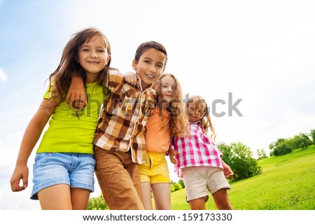 Group of hugging 6 ,7 years kids standing and hugging in the park on summer day - stock photo