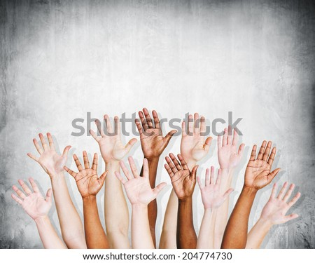 Group of human arms raised with concrete wall. - stock photo