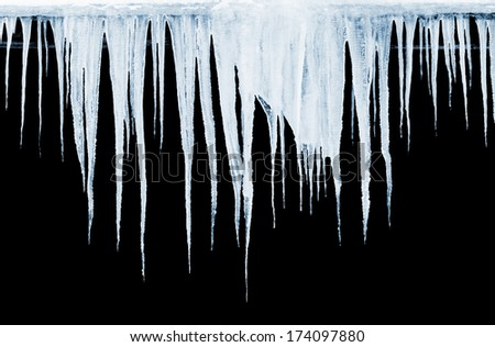 Group of icicles hanging on black background - stock photo