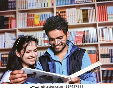 Group of Indian / Asian college students reading a book in the college library. - stock photo