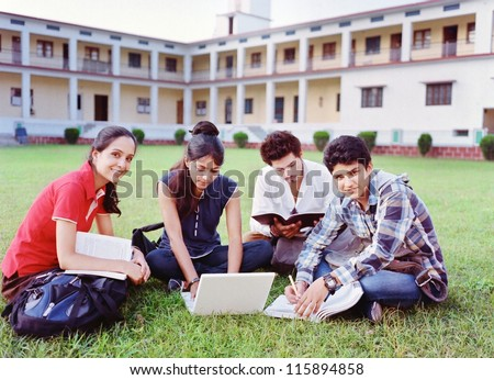 Group of Indian / Asian college students studying over the grass in the campus. - stock photo