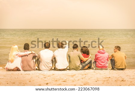 Group of international multiracial friends sitting at the beach talking with each other and contemplating the sea - Concept of multi cultural friendship against racism - Warm vintage filtered look - stock photo