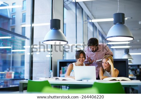 Group of international university students having fun studying in library, three colleagues of modern work co-working space talking and smiling while sitting at the desk table with laptop computer - stock photo