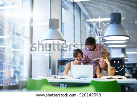 Group of international university students having fun studying in library, three colleagues of modern work co-working space talking and smiling while sitting at the desk table with laptop computer