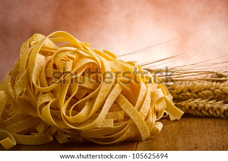 group of italian homemade pasta tagliatelle on wood - stock photo
