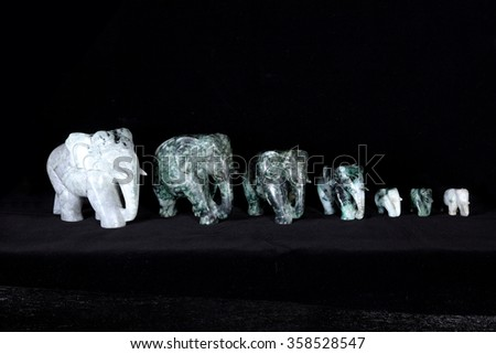 Group of Jade sculpture of elephant isolated on black background.
