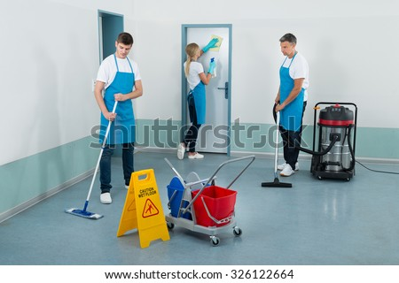 Group Of Janitors Cleaning Corridor With Cleaning Equipments - stock photo