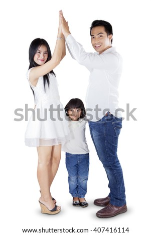 Group of joyful Asian family standing in the studio while playing and having fun together, isolated on white background - stock photo
