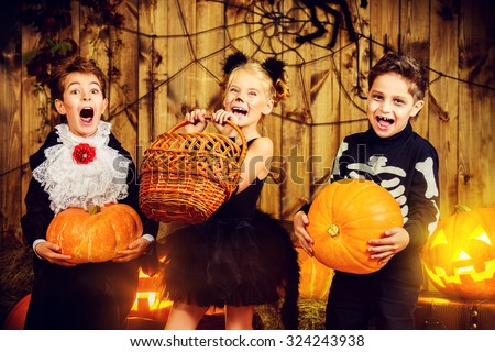 Group of joyful children in halloween costumes posing together in a wooden barn with pumpkins. Halloween concept. - stock photo