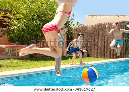 Group of joyful children jumping in a swimming pool in a home garden on a sunny summer holiday, having fun being energetic outdoors. Active kids lifestyle, playing in house exterior on vacation.