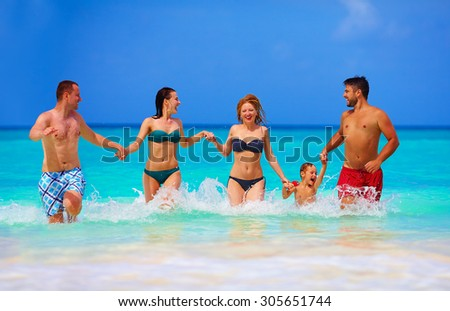 group of joyful friends having fun together on tropical beach