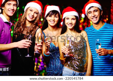 Group of joyful friends in Santa caps toasting at party and looking at camera