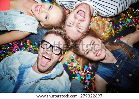 Group of joyful friends lying on the floor in nightclub