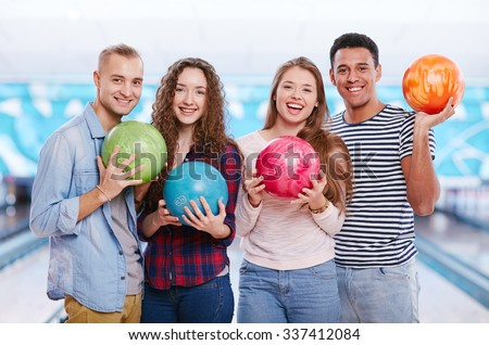 Group of joyful guys and girls with bowling balls