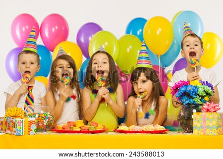 Group of joyful little kids having fun at birthday party. Holidays concept.