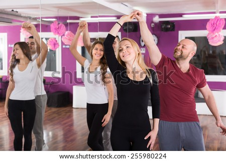 Group of joyful smiling young adults dancing salsa at dance class - stock photo