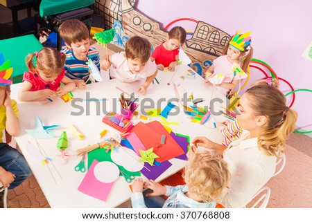 Group of kids and teacher by table view from above - stock photo