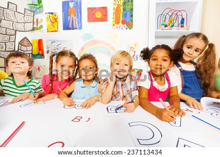 Group of kids, boys and girls in reading class - stock photo