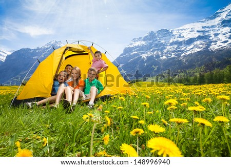 Group of kids, boys and girls sitting together in the tent in dandelion field - stock photo