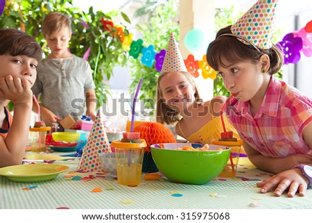 Group of kids celebrating a birthday party with a table of food, sweets and fruit juices in a home garden children party, outdoors. Children friends eating, drinking, playing together, home exterior. - stock photo