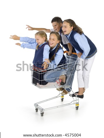 Group of kids having fun: three girls and one boy. They're riding by trolley. Pointing at something. Isolated on white in studio