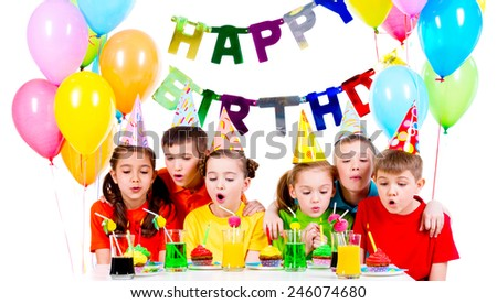 Group of kids in colorful shirts blowing candles at the birthday party - isolated on a white. - stock photo