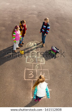 Group of kids jumping on the Hopscotch game drawn on the asphalt after school wearing autumn clothes - stock photo