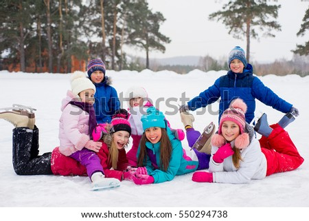 group of kids lying on the ice of the frozen lake with forest on the background