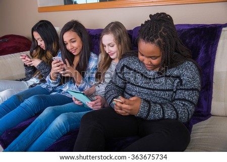 Group of kids on their mobile device - stock photo