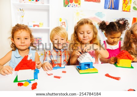 Group of kids playing building houses with plastic blocks sitting together by the table - stock photo