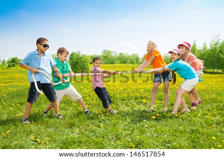 Group of kids playing pulling the rope in the dandelion field - stock photo