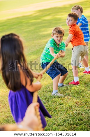 Group of Kids Playing Tug of War On Grass - stock photo