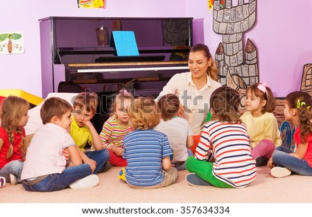 Group of kids sit and listen to teacher tell story - stock photo