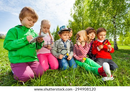 Group of kids sit in the field with magnifier - stock photo