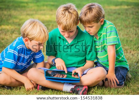 Group of Kids Sitting on grass and using tablet computer - stock photo