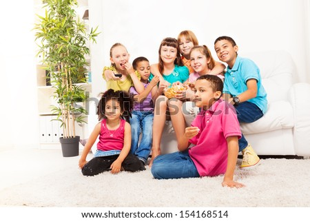 Group of kids sitting on the coach and eat popcorn while watching movie - stock photo